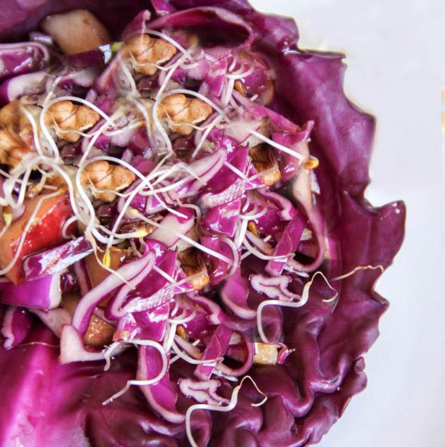 Salade mélangée au chou rouge, noix et graines germées.